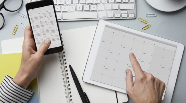 Person looking at calendar on tablet and smartphone