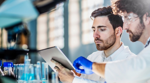 Lab worker pointing to table screen held by other worker