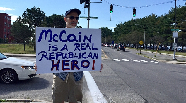 A Portland, Maine man holds a sign in support of Sen. John McCain Friday morning. (Photo by Henry Powderly)