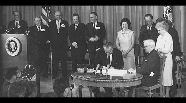 President Lyndon B. Johnson signs the Medicare Bill on July 30, 1965 (Credit: The Harry S. Truman Library)