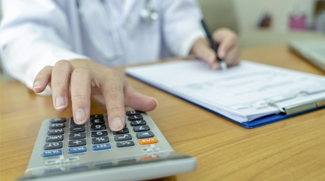 Doctor using a calculator and writing on a pad of paper