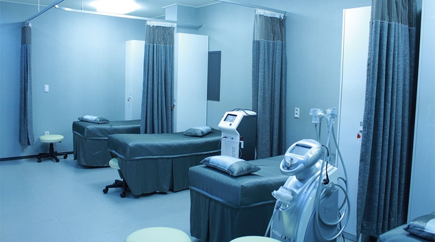 A medical room with three beds and curtains