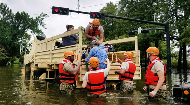 Texas National Guardsmen assist residents affected by flooding caused by Hurricane Harvey onto a military vehicle in Houston on Aug. 27. Army National Guard photo by Lt. Zachary West.