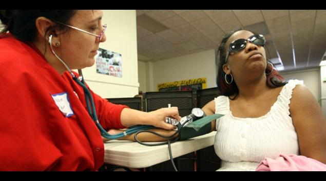 Nurse Allison Miller (L) checks the blood pressure of Keri Anderson in Los Angeles in July 2012. (Getty)