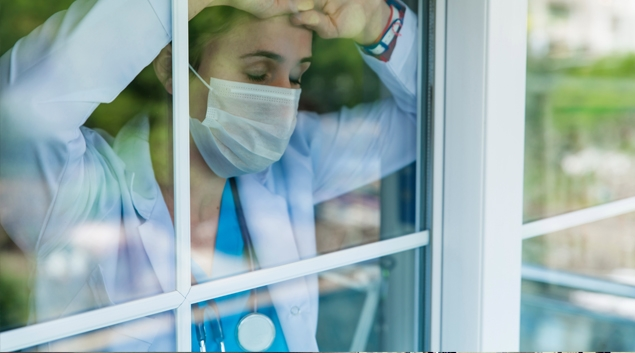 Doctor with mask looking out of a window