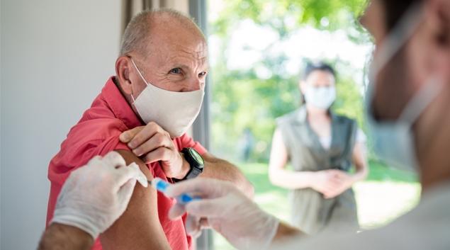 Patient in mask receiving vaccine