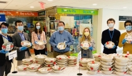 Group of masked people holding salad bowls.