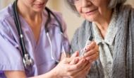 Skilled nurse caring for elderly woman.