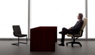 Businessman waiting with empty chair.