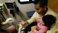 A child of a Mexican immigrant receives free health checkups at a mobile clinic