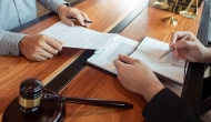 Person with gavel writing in book with someone at desk
