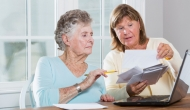 Woman helping senior with medical forms
