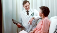 Person in medical jacket consults with person in hospital bed