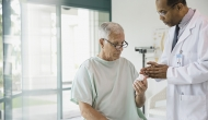 doctor giving male patient prescription bottle at hospital