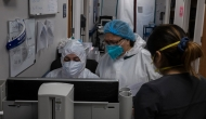 Doctors in PPE looking at a computer screen