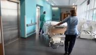 nurse wheeling patient in bed