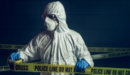 Person in biohazard suit behind police line