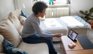 Woman consults a medical professional using telehealth.