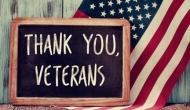 """""""Thank you, veterans"""" sign in front of American flag"""